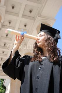 Young student in gown looking at the future through diploma