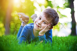 cheerful little boy laying on the grass