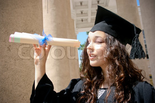 Young student in gown near the university with diploma