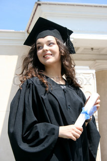 Young caucasian smiling student in gown near the university