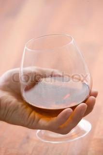 Hånd der holder et glas med cognac