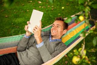 male in a hammock with a digital tablet