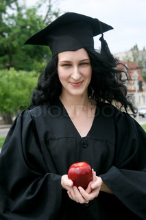 Caucasian student girl in gown with apple