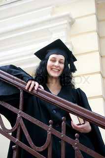 Young laughing student in gown near the university