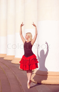 Ballerina with hands raised in pointe i