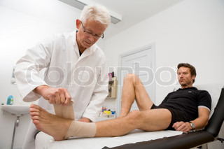A doctor putting bandage on a man's foot