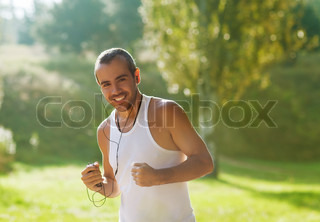 boy running in the park and listening to player