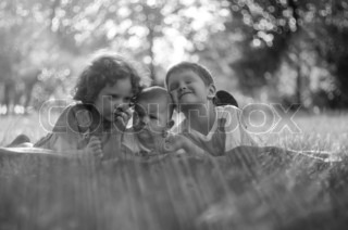 Little girl and boy lying in the sun on the grass, black and white photo