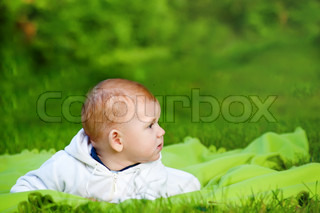 Beautiful little baby lying on the grass in the park