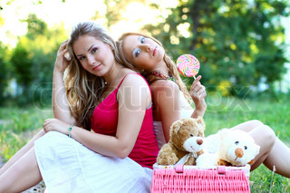 Two beautiful caucasian women with lollipop