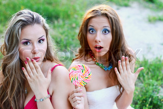 Two pretty caucasian girls with lollipop surprised