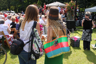 The standing young girls with striking shoulder bags listen to the music from the platfrom in this park, nice concert.