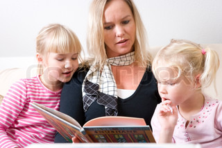 A caucasian mother reading a book to her daughters