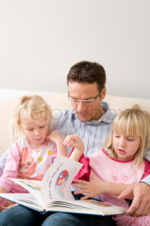 A caucasian father reading a story to his daughters
