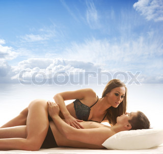 Young and beautiful couple having sex over sky and sea background