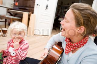 A music teacher playing the guitar for children