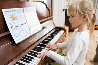 A young girl learning to play the piano
