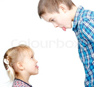 Sister and brother stick out tongues to each other stock photo