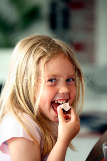 close headshot of happy little girl eating chocolate and vanilla cake