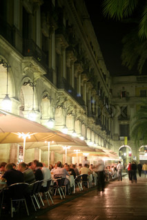 Blurred image of people sitting in outdoor cafe in Barcelona square at night