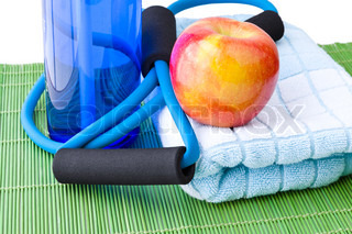 Healthy lifestyle concept - bottle of water, apple, expander and towel