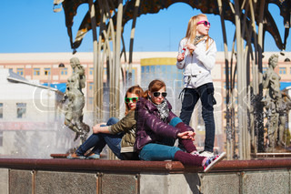 Teenage girls relaxing against a city fountain