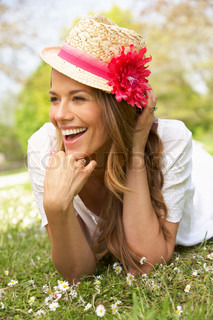 Woman Lying In Field Of Summer Flowers With Straw Hat