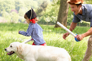 Father Playing Exciting Adventure Game With Son And Dog In Summer Field