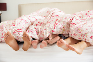 Family's Feet Poking Out From Duvet In Bed