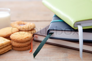 Notebook stack and some dessert on table
