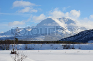 Snow covered mountain in winter with frozen river in the front