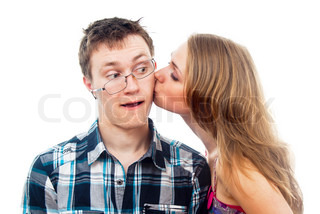 girl kisses a boy on the cheek