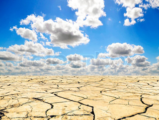 Drought landscape against bright blue sky with clouds