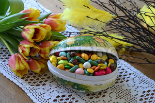 Easter eggs with Easter candy on a table with tulips and twigs