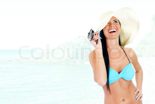 Young woman in bikini and straw hat on a seashore background
