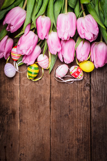 Tulips and eggs border over wooden backdrop Easter decorations