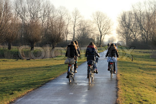The girlfriends, rucksack on the back of the bike, going over the cycle path to school in the morning in fall.