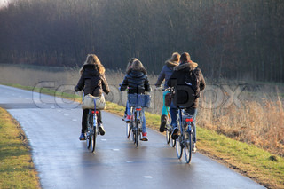 The boy and the girlfriends, their rucksack  on the back of the bicycle, biking over the cycle path to school in fall.