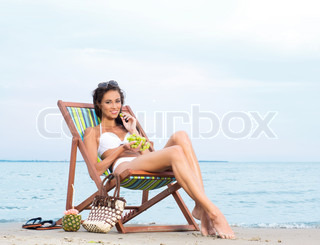 Young, beautiful, sporty and sexy woman eating grapes on the beach