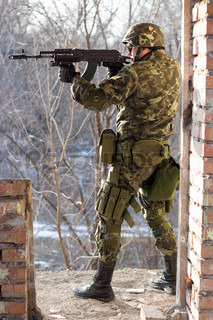 Soldier standing near wall with a gun