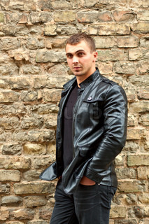 brutal young sexual man in a leather jacket