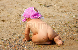 Fun photo of the naked baby girl playing with sand on the beach