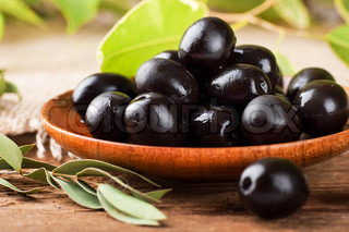 Black olives in a wooden plate and a rough board
