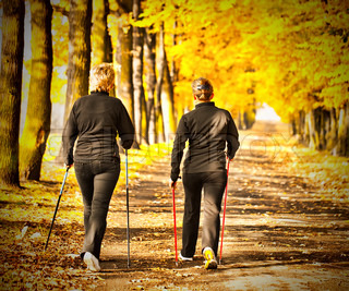 Two women in the park in the autumn - Nordic walking