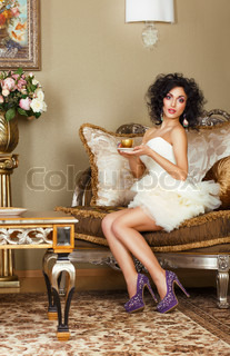 Luxurious Lady sitting on Retro Couch with Cap of Coffee Classic Interior