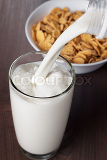 milk pouring into glass and bowl with cornflakes