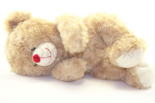 Cute teddy bear is lying isolated on white