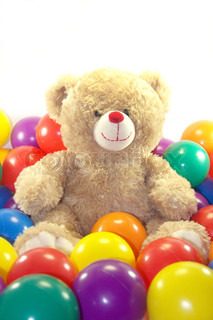 Teddy bear is sitting in colorful balls