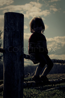 Silhouette of a young girl on the fence