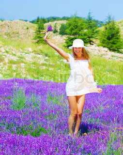 Cute girl wearing white hat holding in hand beautiful purple lavender flowers, dancing on floral glade, summer time season